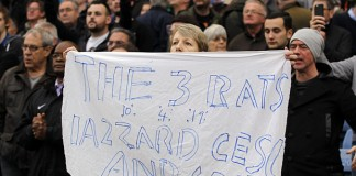 A supporter holds a banner against certa